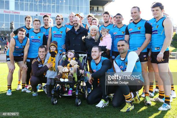 Hawks coach Alastair Clarkson, recovering from serious illness, introduces a Hawks fan to the players and poses for a photograph during a Hawthorn...