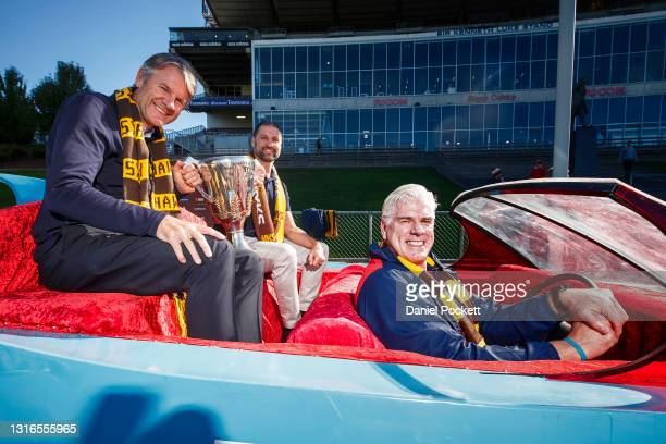 Hawks legends Gary Ayres , Darrin Pritchard and Andrew Gowers pose for a photograph in the 'Batmobile' from the 1991 AFL Grand Final during a...