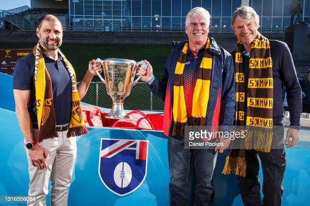 Hawks legends Gary Ayres , Darrin Pritchard and Andrew Gowers pose for a photograph with the 1991 AFL Premiership Cup in front of the 'Batmobile'...
