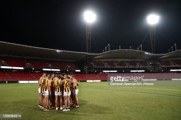 Hawks players huddle during the round 6 AFL match between the Collingwood Magpies and the Hawthorn Hawks at GIANTS Stadium on July 10 2020 in Sydney...