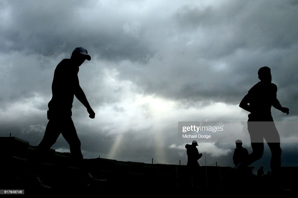 Hawks players walk out as a storm whips through in the background during a Hawthorn Hawks AFL training session on February 14, 2018 in Melbourne, Australia.