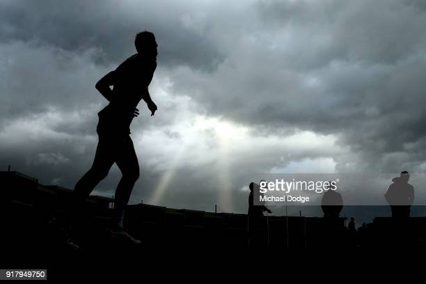 Hawks players walk out as a storm whips through in the background during a Hawthorn Hawks AFL training session on February 14 2018 in Melbourne...