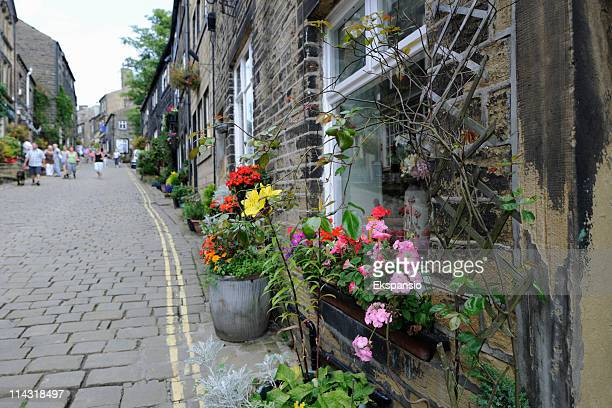 haworth high street with cobblestones and millstone grit terraced houses - bradford england stock pictures, royalty-free photos & images