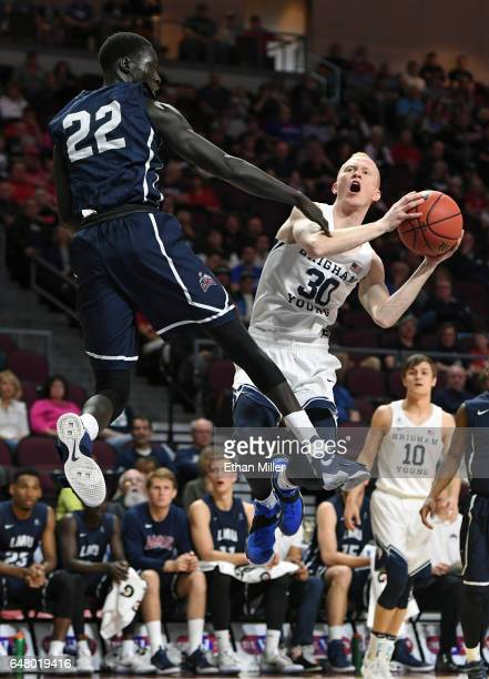 Haws of the Brigham Young Cougars drives to the basket against Buay Tuach of the Loyola Marymount Lions during a quarterfinal game of the West Coast...