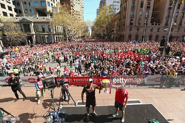 Hawthorn Hawks captain Luke Hodge and Sydney Swans captain Kieren Jack hold aloft the Grand Final trophy during the 2014 AFL Grand Final Parade on...