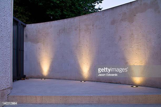 LED lighting in brass fixtures illuminate a concrete wall and step.