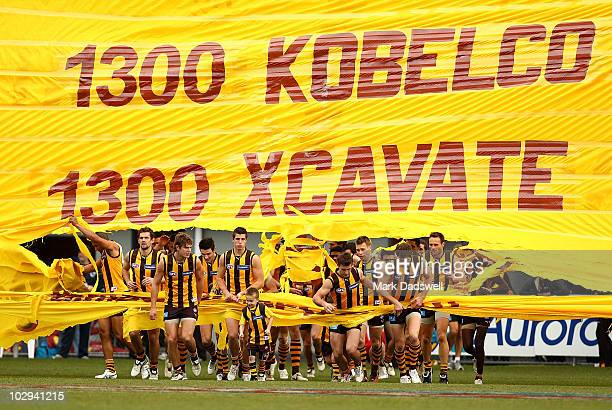 Hawthorn players run through the banner at the start of the round 16 AFL match between the Hawthorn Hawks and the Brisbane Lions at Aurora Stadium on...