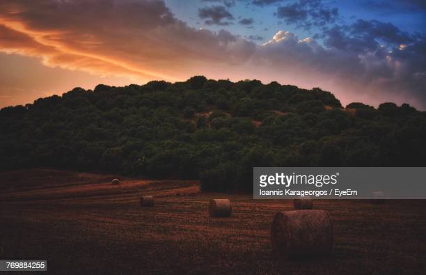 Hay Bales On Field Against Sky At Sunset
