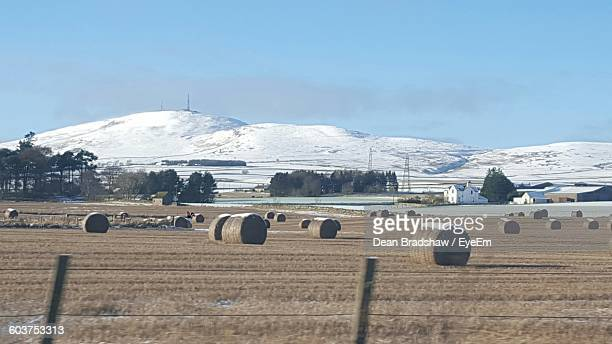 Hay Bales On Field Against Snowcapped Mountains