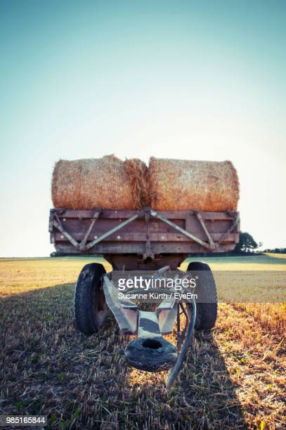hay bales on vehicle trailer against clear sky at farm - stroh stock-fotos und bilder