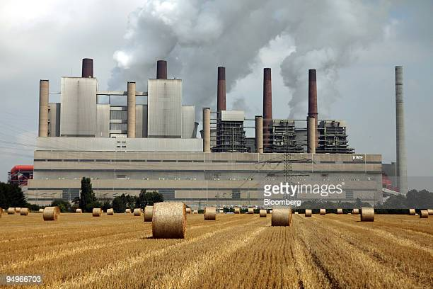 Hay bales stand in a field in front of the RWE AG owned coalfired power station in Niederaussem Germany on Tuesday Aug 11 2009 RWE announce earnings...