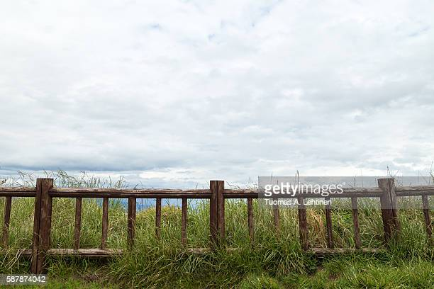 Hay, grass, an old wooden railing and cloudy sky with copy space.