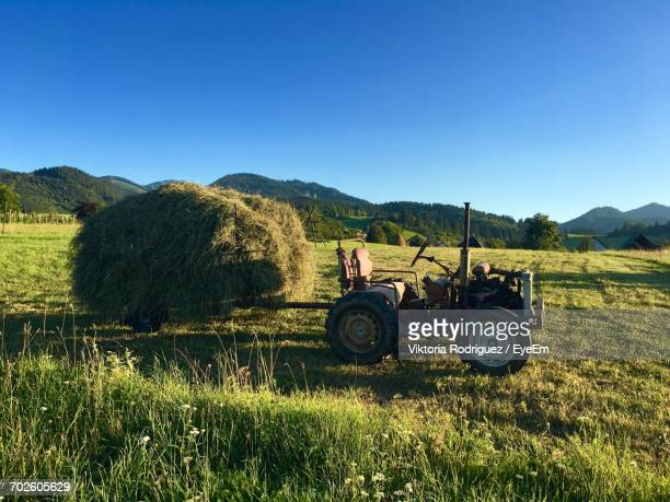 hay on tractor trailer at farm field against clear blue sky - stroh stock-fotos und bilder