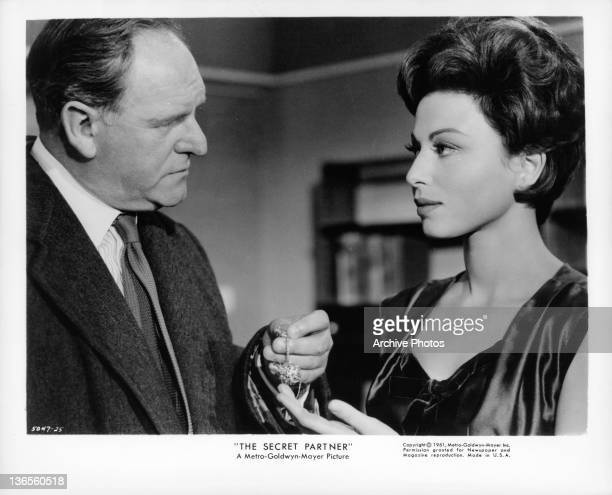 Haya Harareet accepting a piece of jewelry from actor Bernard Lee in a scene from the film 'The Secret Partner' 1961