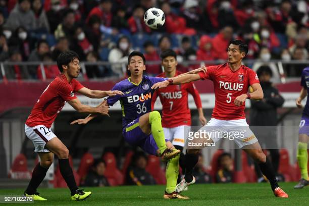Hayao Kawabe of Sanfrecce Hiroshima competes for the ball against Tomoaki Makino and Yuki Abe of Urawa Red Diamonds compete for the ball during the...