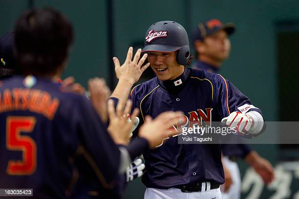 Hayato Sakamoto of Team Japan is greeted in the dugout after scoring a run in the top of the third inning during Pool A Game 1 between Team Japan and...