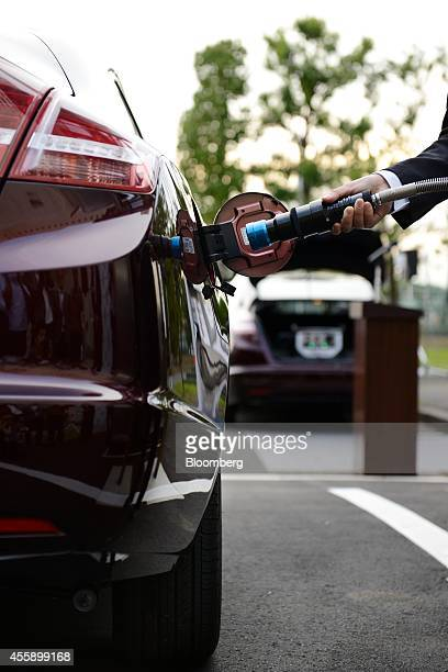 Hayato Shimizu mayor of Saitama holds the fueling nozzle of the smart hydrogen fueling station as he poses for a photograph during the unveiling of...