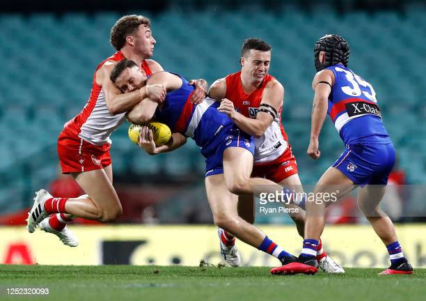 Hayden Crozier of the Bulldogs is tackled by Will Hayward of the Swans during the round 4 AFL match between the Sydney Swans and the Western Bulldogs...