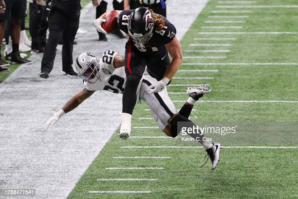 Hayden Hurst of the Atlanta Falcons hurdles Keisean Nixon of the Las Vegas Raiders for a first down in the second quarter of their NFL game at...