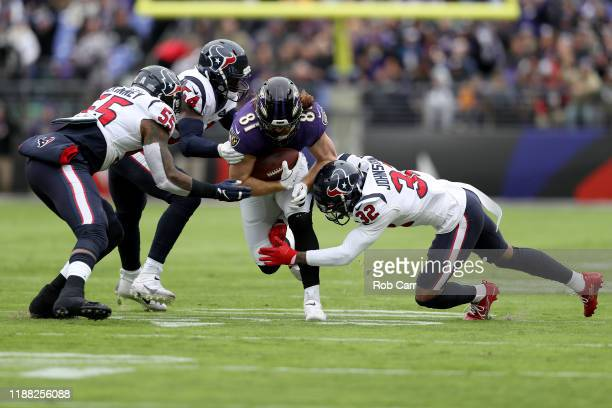 Hayden Hurst of the Baltimore Ravens gets tackled by Lonnie Johnson of the Houston Texans during the second quarter in the game at MT Bank Stadium on...
