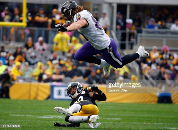Hayden Hurst of the Baltimore Ravens hurdles Joe Haden of the Pittsburgh Steelers in the first half on October 6 2019 at Heinz Field in Pittsburgh...