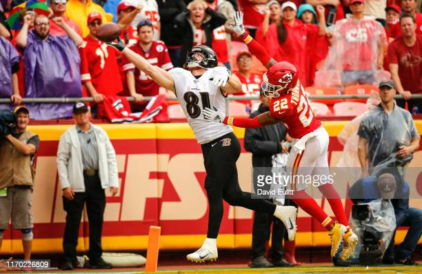 Hayden Hurst of the Baltimore Ravens reaches for a pass in the end zone with pressure form Juan Thornhill of the Kansas City Chiefs at Arrowhead...