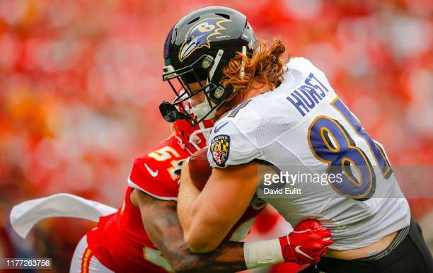 Hayden Hurst of the Baltimore Ravens recoils during a tackle by Damien Wilson of the Kansas City Chiefs at Arrowhead Stadium on September 22 2019 in...