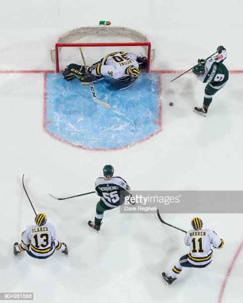 Hayden Lavigne of the Michigan Wolverines makes a save Mitchell Lewandowski of the Michigan State Spartans during the consolation game of the Great...