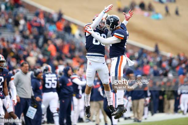 Hayden Mitchell and Terrell Jana of the Virginia Cavaliers celebrate a touchdown in the first half during a game at Scott Stadium on November 23 2019...