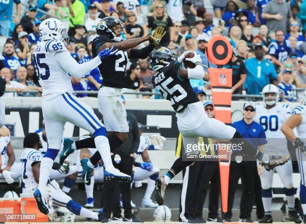 J Hayden of the Jacksonville Jaguars leaps for the football in front of Eric Ebron of the Indianapolis Colts during their game at TIAA Bank Field on...