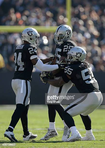 Hayden of the Oakland Raiders, Charles Woodson of the Oakland Raiders and Sio Moore of the Oakland Raiders celebrate an interception in the first...
