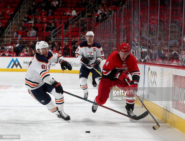Haydn Fleury of the Carolina Hurricanes moves the puck along the boards past Yohann Auvitu of the Edmonton Oilers during an NHL game on March 20 2018...