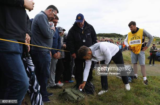 Haydn McCullen of England moves his ball as it lands on the bag of a spectator during the second round of the 146th Open Championship at Royal...