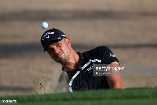Haydn Porteous of South Africa plays his second shot from a bunker on the 15th hole during day three of Omega Dubai Desert Classic at Emirates Golf...