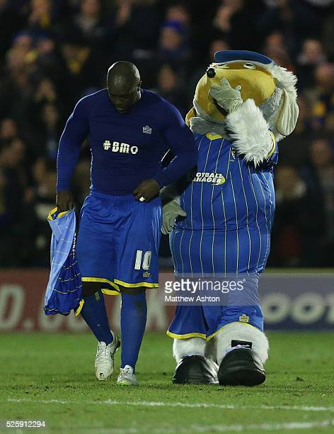 Haydon the Womble mascot consoles a dejected Adebayo Akinfenwa of AFC Wimbledon at the end of the match