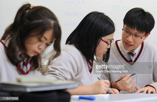 Hayley Anne Thomas Andrea Hui and Gordon Choi Gachun from Creative Secondary School in discussion during debating competition against St Paul's...