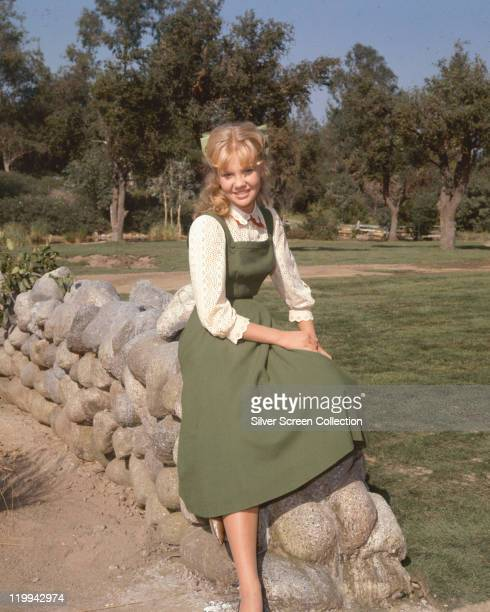 Hayley Mills British actress smiling as she poses sitting on a drystone walll wearing a green dress circa 1960