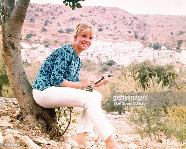 Hayley Mills British actress wearing a blue blouse and white trousers and sitting at the base of a tree holding a small stringedinstrument circa 1965
