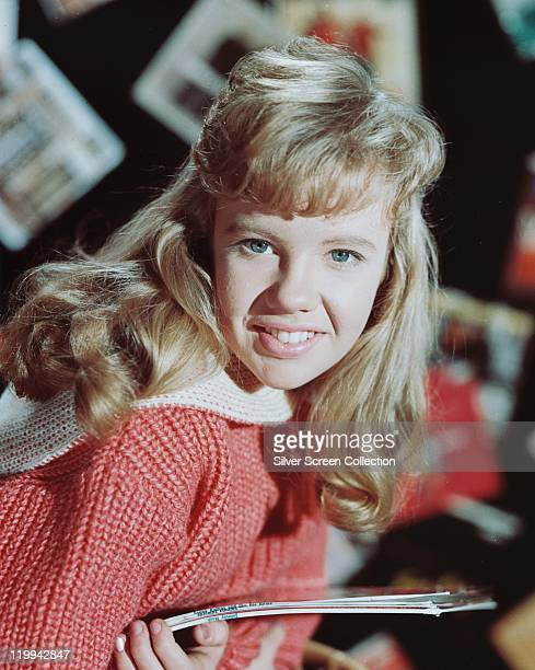Hayley Mills British actress wearing a coral pinkandwhite knitted jumper and smiling while holding a number of LP record sleeves circa 1960
