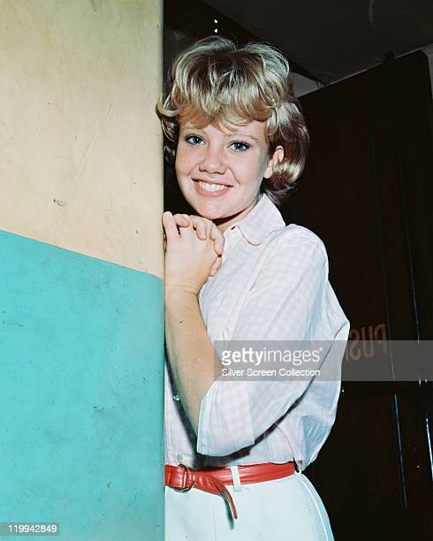 Hayley Mills British actress wearing a white dress tie around the waist with a red belt smiling as she poses against a blueandwhite wall circa 1960