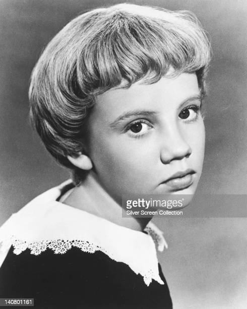 Hayley Mills British actress with her hair in a pageboy hairstyle wearing a black top with white lace trim in a studio portrait against a grey...