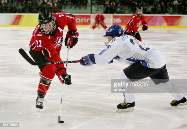 Hayley Wickenheiser of Canada fights to take a shot around Karoliina Rantamaki of Finland during the women's ice hockey semifinals game against...
