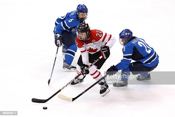 Hayley Wickenheiser of Canada handles the puck against Michelle Karvinen and Jenni Hiirikoski of Finland during the ice hockey women's semifinal game...