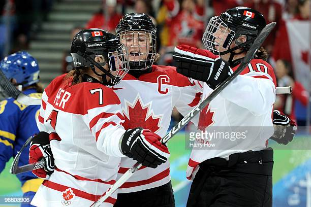 Hayley Wickenheiser of Canada is congratulated by teammates after scoring her team's eighth goal during the ice hockey women's preliminary game...