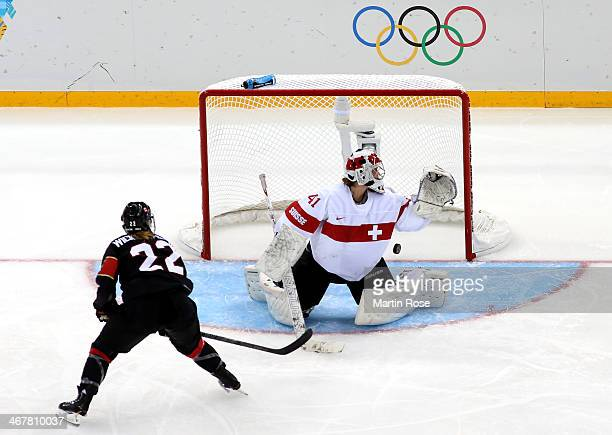 Hayley Wickenheiser of Canada scores a goal against Florence Schelling of Switzerland in the second period during the Women's Ice Hockey Preliminary...