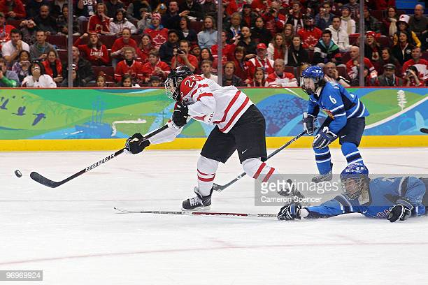 Hayley Wickenheiser of Canada shoots the puck as Saija Sirvio of Finland dives after her in the third period during the ice hockey women's semifinal...