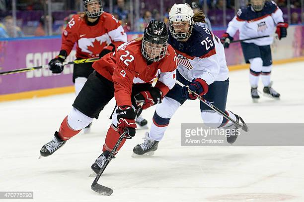 Hayley Wickenheiser of the Canada controls the puck as Alex Carpenter of the USA pursues during the first period of the women's gold medal ice hockey...