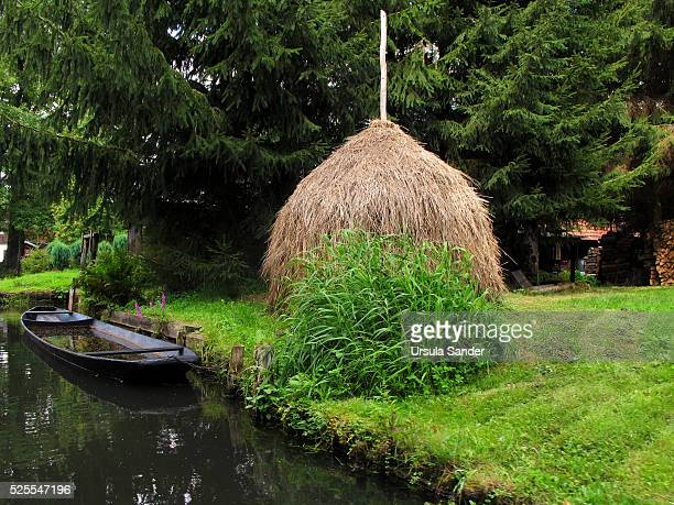 Haystack and flooted boat on canal in Spree Forest, Brandenburg, Germany
