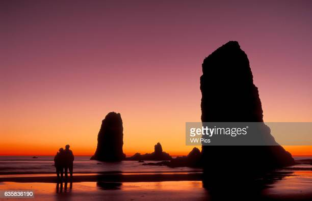 Haystack Rock sea stacks at sunset with couple on beach Cannon Beach Oregon coast