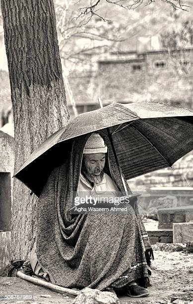 A hazara elderly man reciting holy Quran while its raining in a graveyard as a prayer for one of his lost relatives died during a massive...